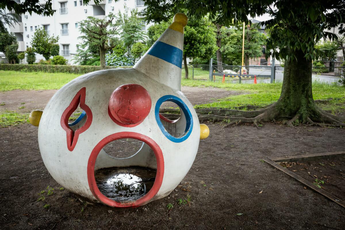 a disturbing concrete clown head in a Japanese playground