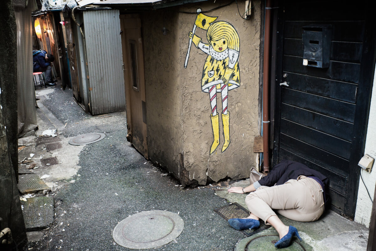 Japanese woman passed out drunk in a dirty Tokyo alleyway