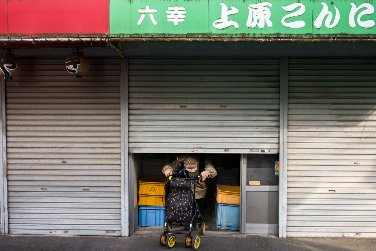 old lady in old Tokyo exiting her old shuttered shop