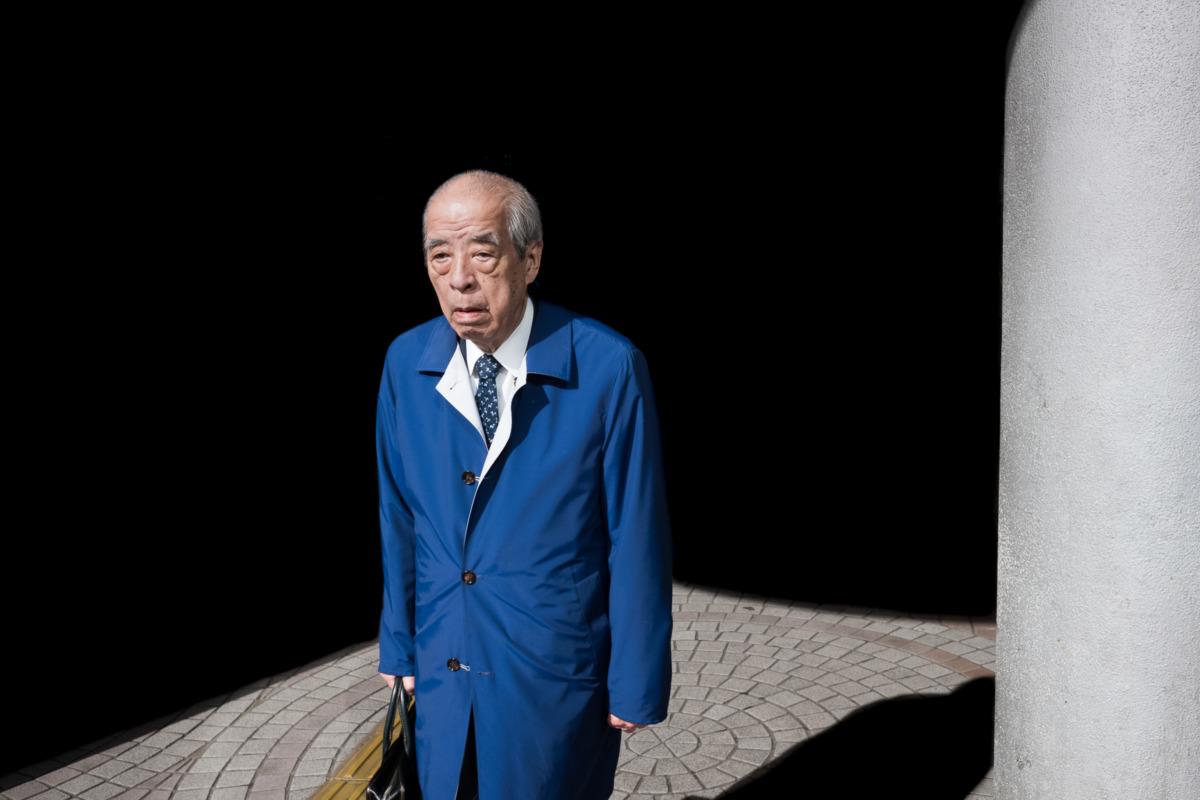 an old Tokyo salaryman dressed in blue