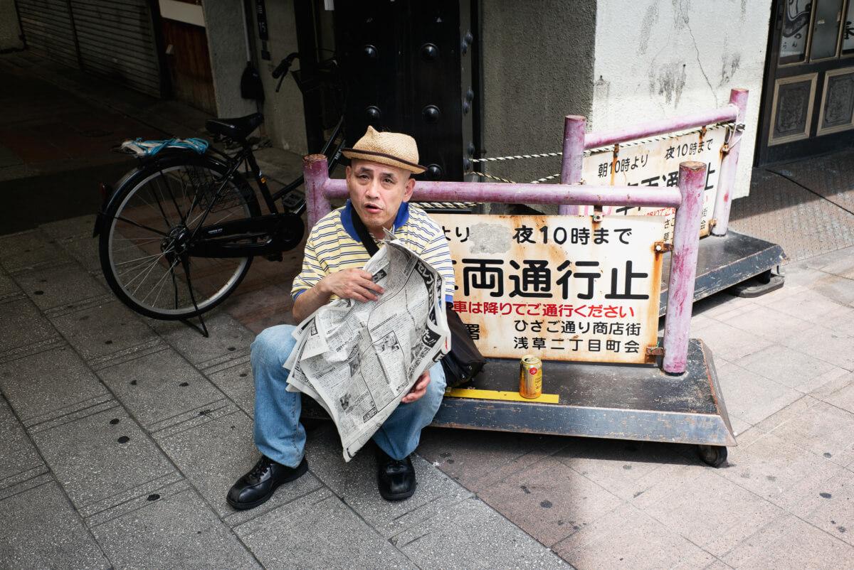 tokyo newspaper reader in the street