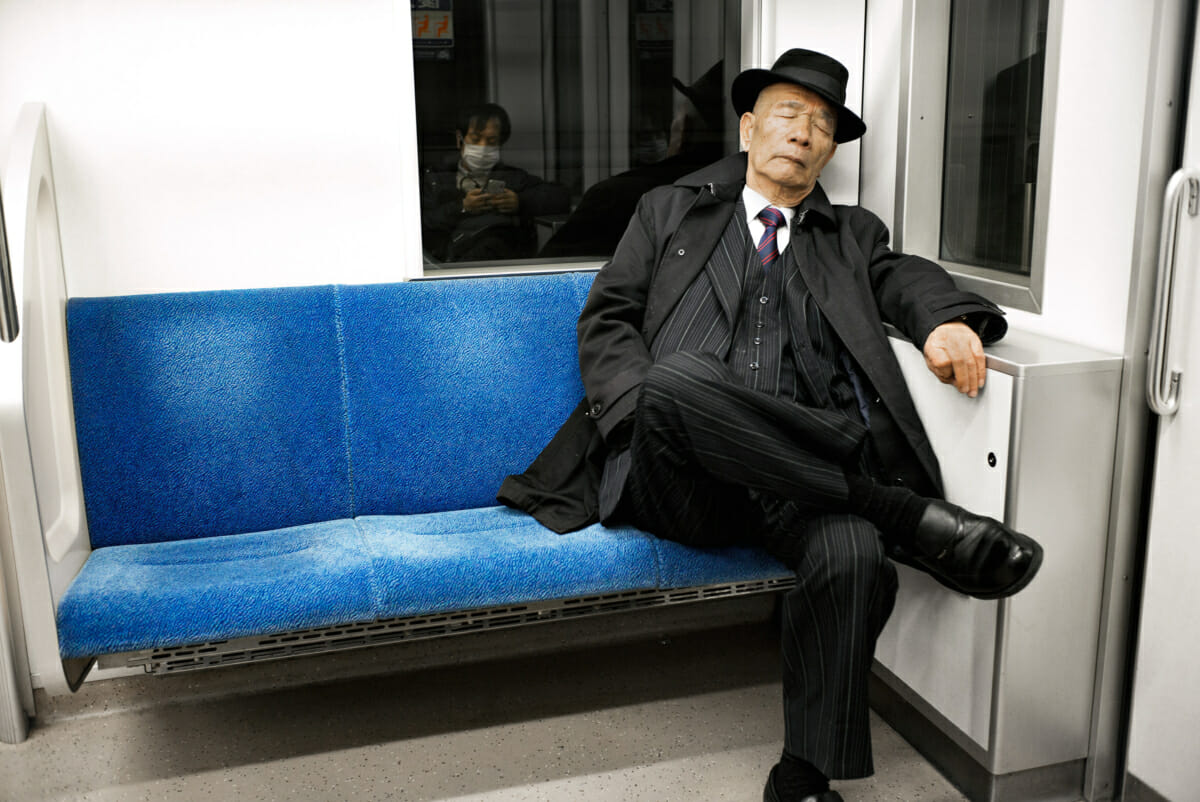 old school tokyo train traveller in pinstripes and trilby