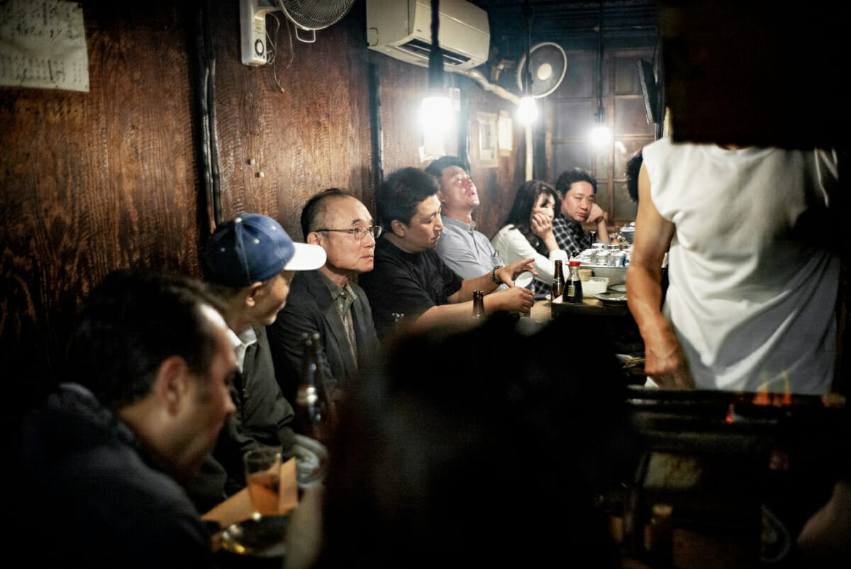 unhappy Japanese drinkers in a small Tokyo bar